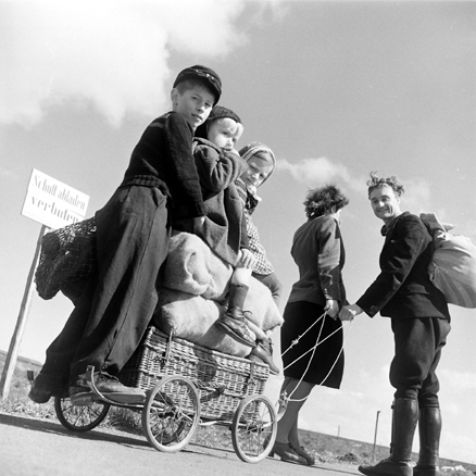 A Couple pulling a handcart loaded with children and supplies, Germany, 1945