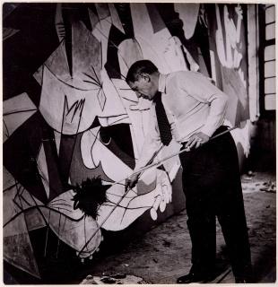 """Pablo Picasso de pie trabajando en Guernica en su taller de los Grands-Augustins, mayo-junio 1937 Foto: Dora Maar. Museo Nacional Centro de Arte Reina Sofía, Madrid. © Sucesión Pablo Picasso, VEGAP, Madrid 2017 — Cortesía de Obra Social """"la Caixa"""""""