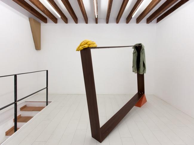 HOMENAJE A GERARDO RUEDA, 230x170x20 cm. Estructura de madera, ángulos metálicos, estructura triangular forrada de tela, chaqueta y plátanos. 2014/2019 — Cortesía de Carlos Maciá