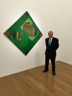 """Guillermo Ruberto junto a una obra de su colección del artista Rogelio Polesello con motivo de la exposición """"Polesello Joven 1958-1974"""", celebrada en el MALBA en 2015."""