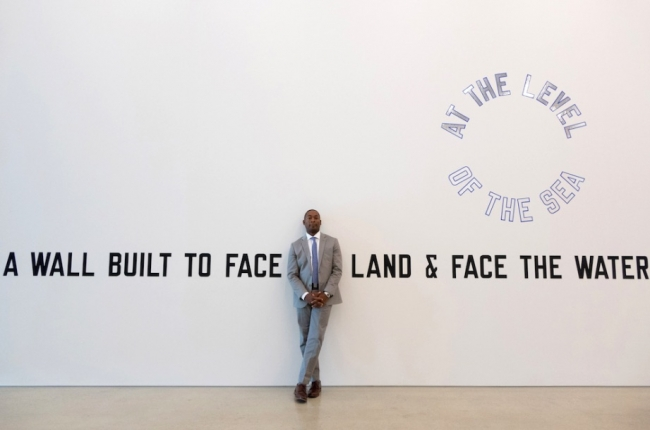 El director del PAMM, Franklin Sirmans posando junto a la obra del artista Lawrence Weiner, A WALL BUILT TO FACE THE LAND & FACE THE WATER AT THE LEVEL OF THE SEA, 2008. Foto de Angel Valentin. Cortesía del Pérez Art Museum Miami | El Museo del Barrio y el Pérez Art Museum Miami, entre los nuevos aliados de Frieze Nueva York