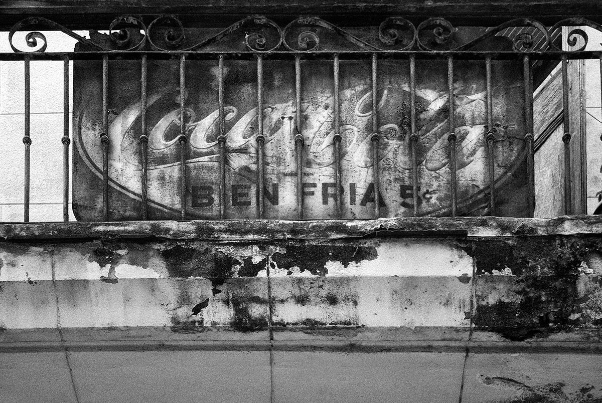 Coca Cola bien fría. Anuncio del más impotante refresco producido en la isla de Cuba antes de 1959 reapareciendo ahora entre los barrotes de un antiguo balcón en el corazón de la Habana Vieja. (2016) - Dany del Pino Rodríguez